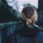 woman facing a long bridge
