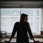 woman leaning on kitchen counter alone