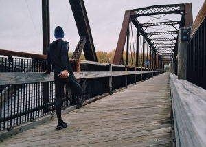 man stretching on a bridge