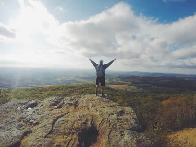 man with arms raised on top of a mountain